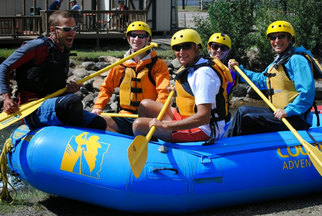 a whitewater rafting guide poses with a small group of people holding their paddles and ready to raft