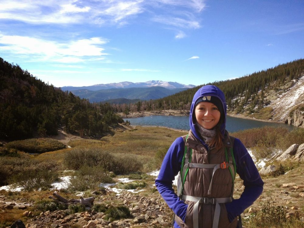 woman smiles in front of a panoramic view of the rocky mountains at st marys glacier near idaho springs colorado