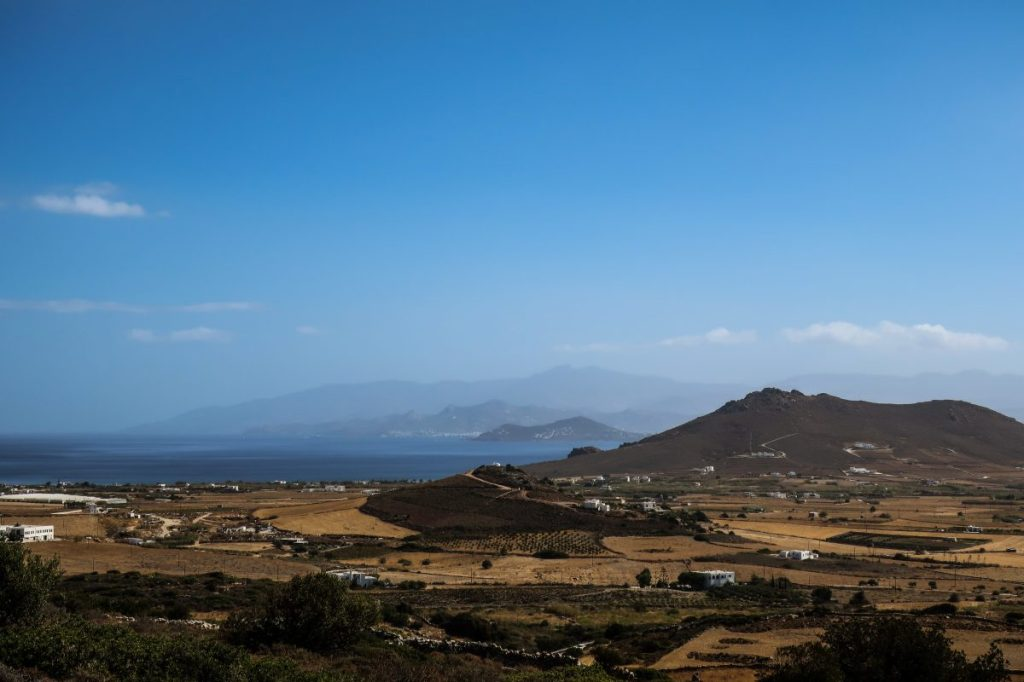 View from the Byzantine Road in Paros, Greece, with the Greek farmland stretching out to the coastline. The mountains of Naxos are on the horizon on a beautiful clear day.