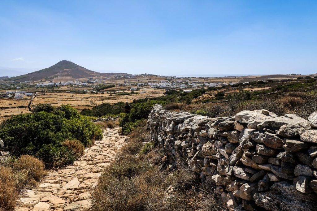 a rocky path carves its way through the Greek country side. A stacked rock wall a few feet high follows the path which is framed by dark green shrubs and looks out across farmland dotted with white buildings