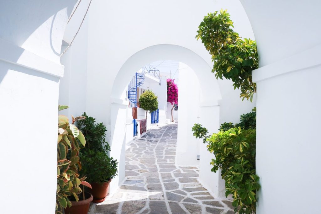 A stone paved path leads through all-white archways, with lush green plants, hot pink bougainvillea, and blue spiral staircases leading up to homes.