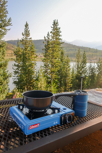 coleman one burner butane campstove on a picnic table in front of a mountain lake