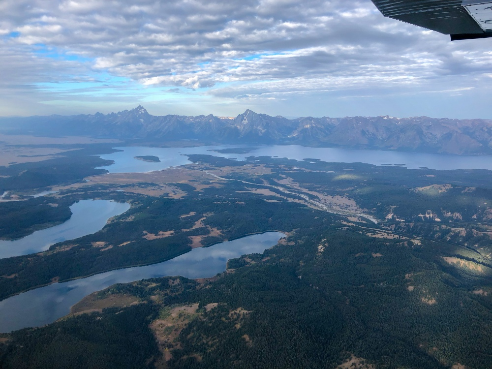 an aerial view from a flightseeing plan of Grand Teton National Park. the park's biggest lakes and evergreen forests stretch out in front of the rugged mountain range in the early morning light