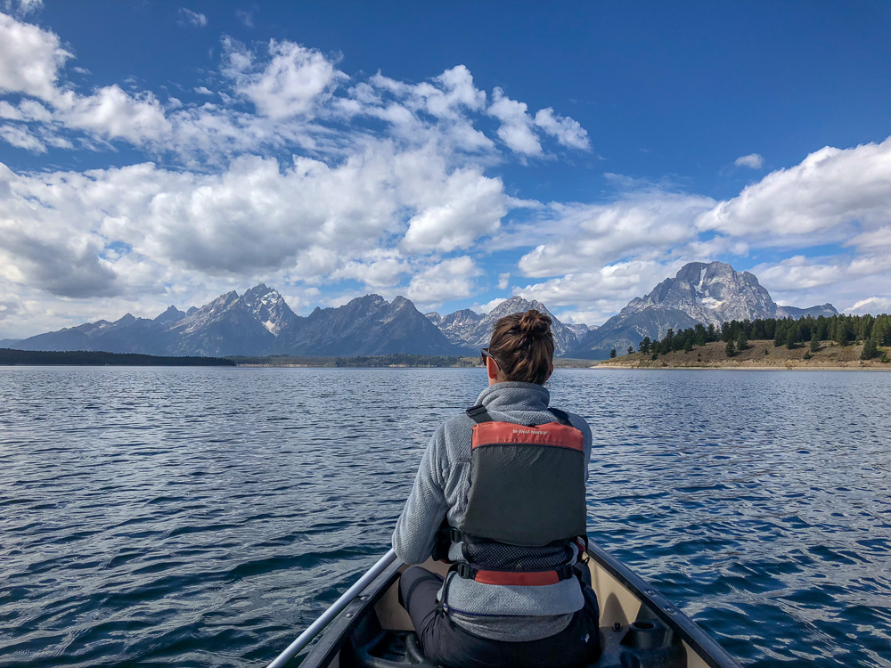 woman canoeing on Jackson Lake in Grand Teton park. The lake lays out ahead of her, bordered by the Grand Tetons under a bright blue sky.