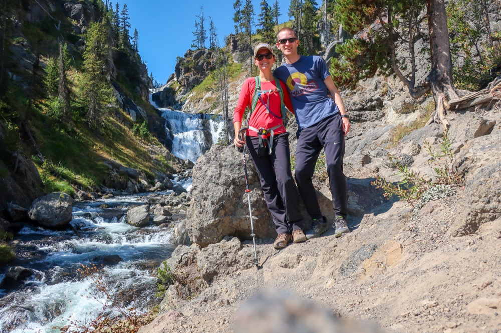 a couple in hiking clothes pose for a picture in front of mystic falls, a large waterfall in yellowstone national park