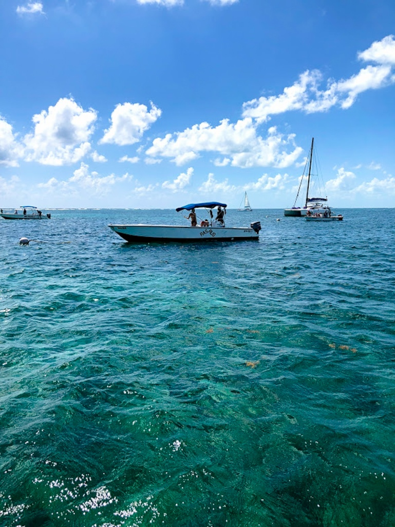 boats sit on teal tropical water under a bright blue sky in belize
