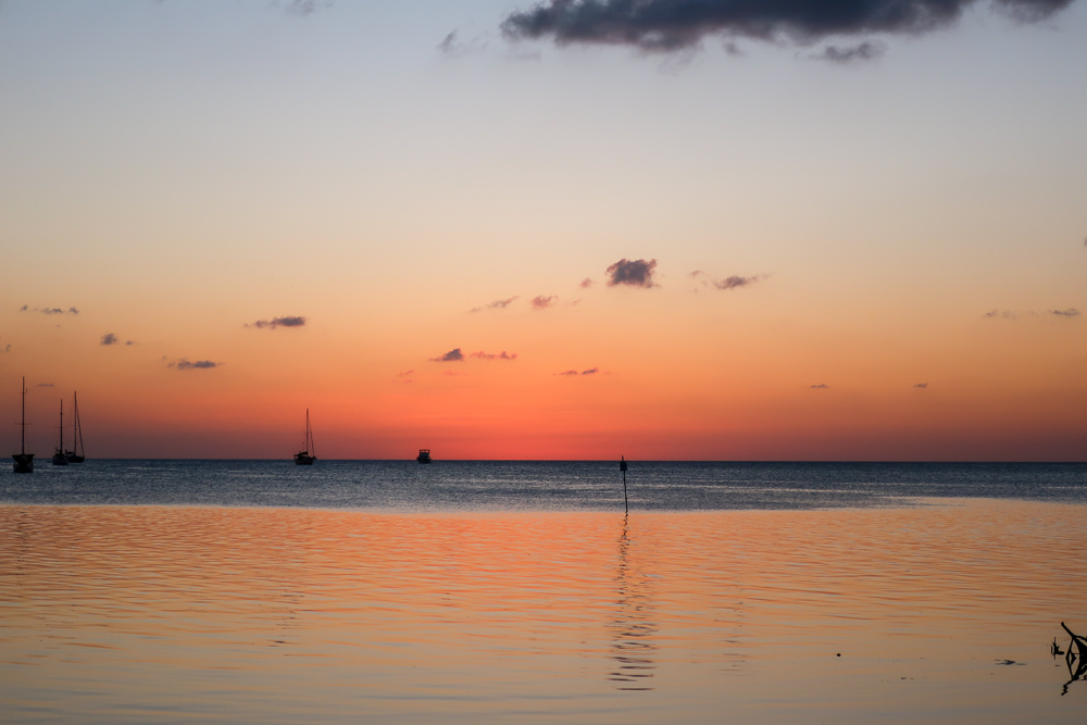 the sky is lit up orange at sunset in caye caulker belize. sailboats are visible on the horizon and the sunset reflects off the water.