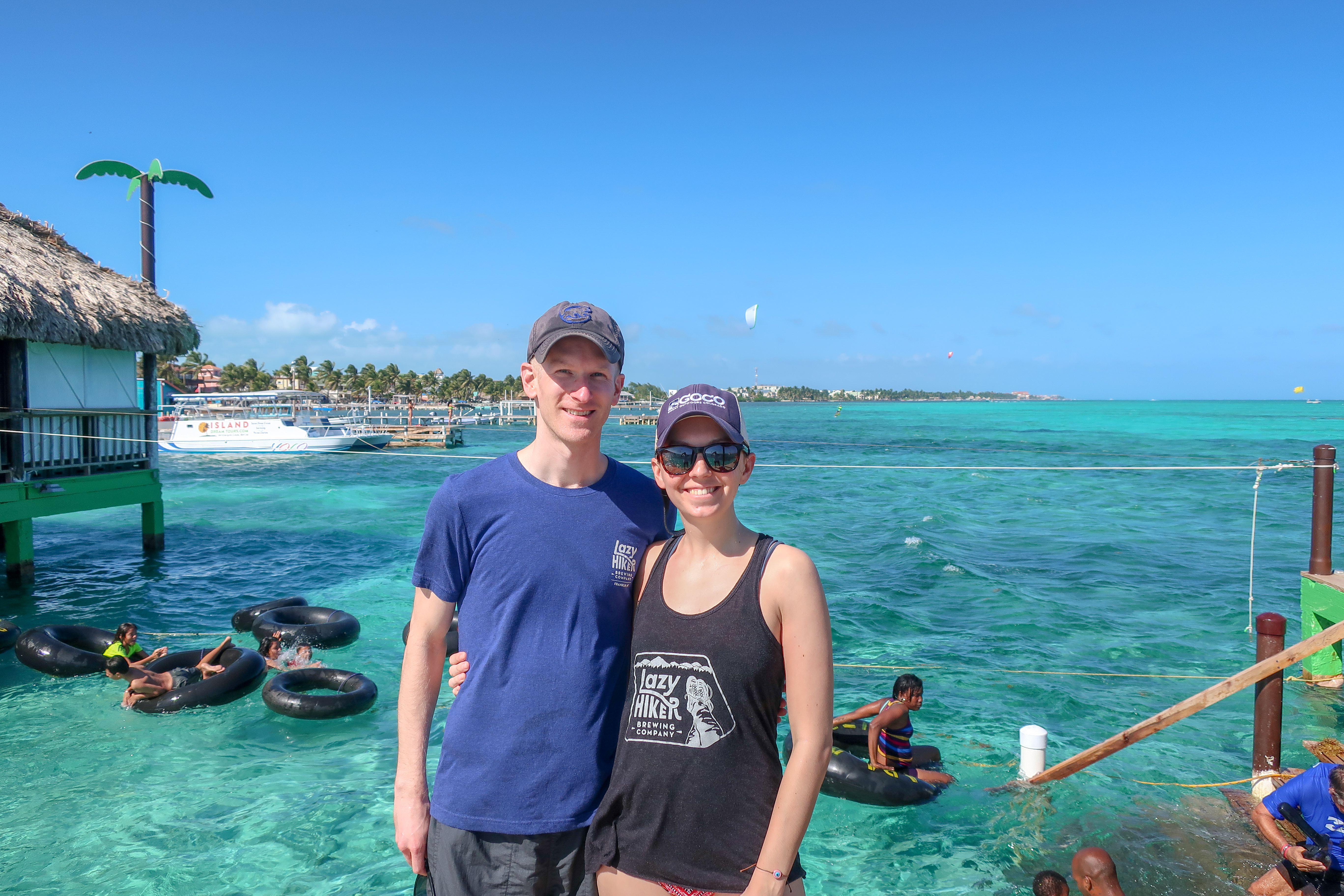 a couple stand in front of the turquoise water at the palapa bar in san pedro belize. Children on inner tubes float in the water behind them.