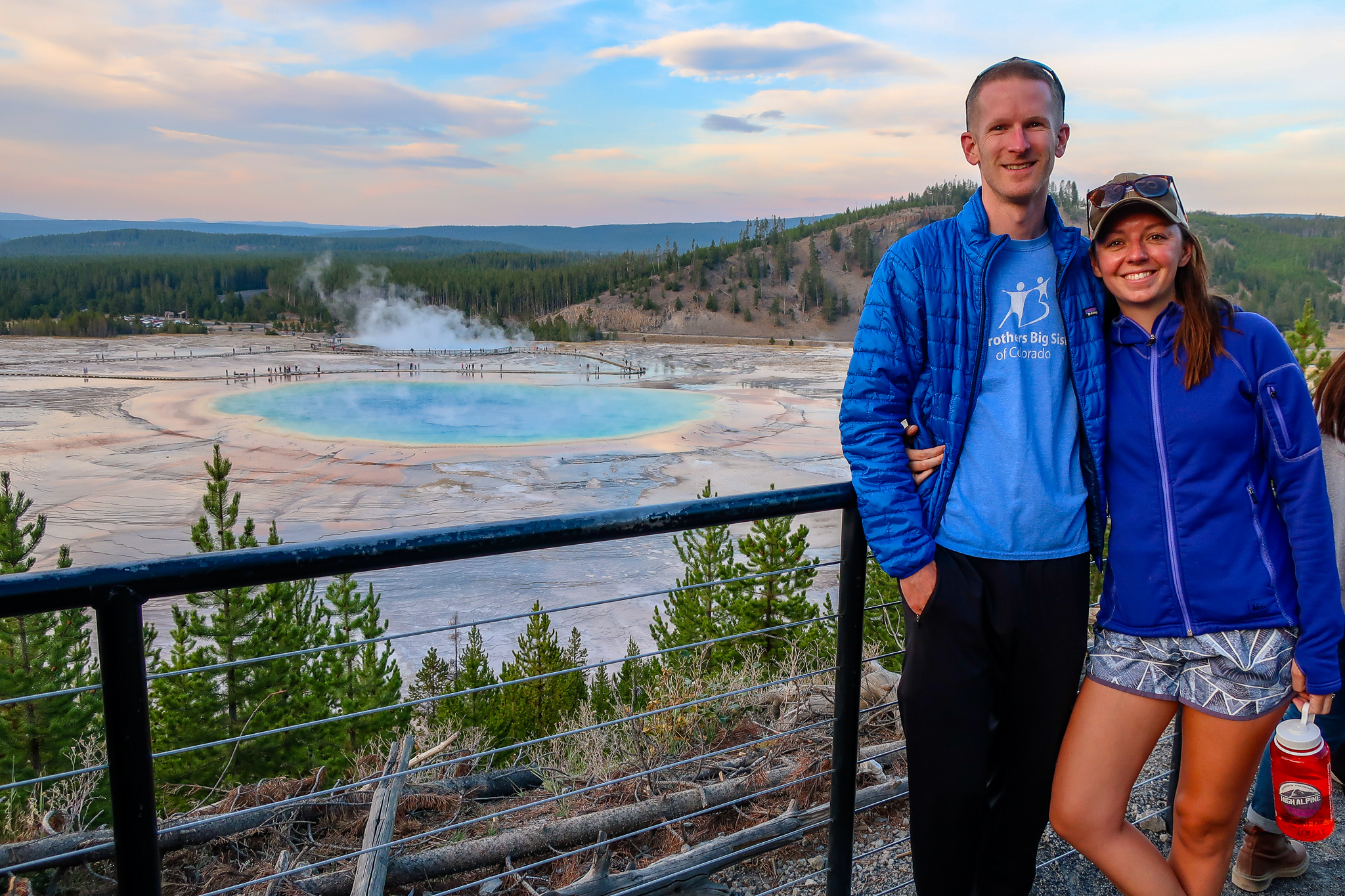 couple stands at the grand prismatic hot spring overlook in yellowstone national park at sunset