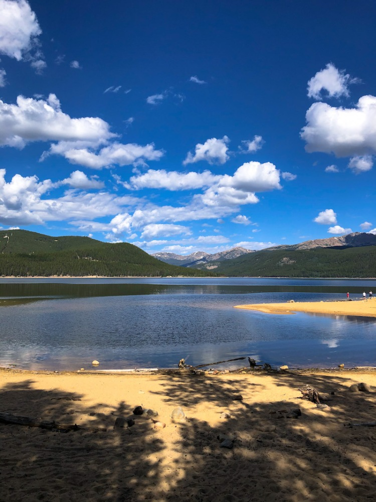 turquoise lake leadville colorado looking west toward the mountains on a sunny day. a sandy beach is in the foreground.